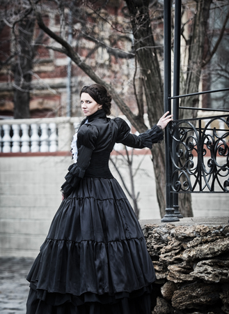 Outdoors portrait of a victorian lady in black 스톡 콘텐츠