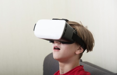 Boy wearing virtual reality 3D glasses lives in a virtual world