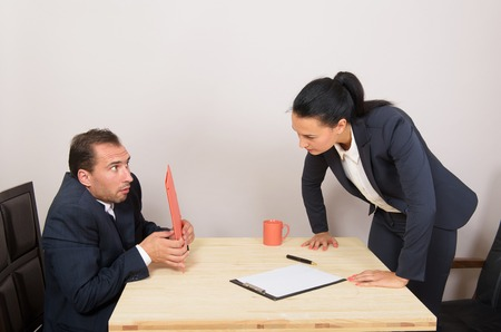 Angry businesswoman reproaching afraid man at work in the office