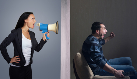 Man watching TV while angry woman calling him through a megaphone