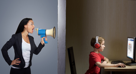 Tween son in headphones looks at a computer screen while his mother shouts at him through a megaphone Banco de Imagens