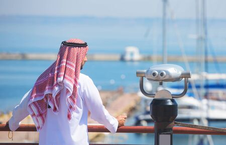 thobe: Arabian man looking at the yacht harbor, back view