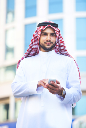 Outdoors portrait of a handsome arabian man using a smart phone Stock Photo