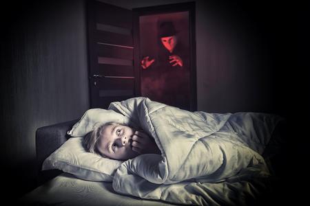 悪夢のような。戸口にマスク見知らぬ人立ちながらベッドで横になっている怖い少年