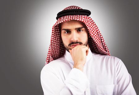 thobe: Studio portrait of a pensive handsome Arabian man Stock Photo