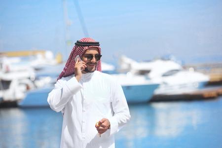 thobe: Arabian man talking on the cell phone at the yacht harbor Stock Photo