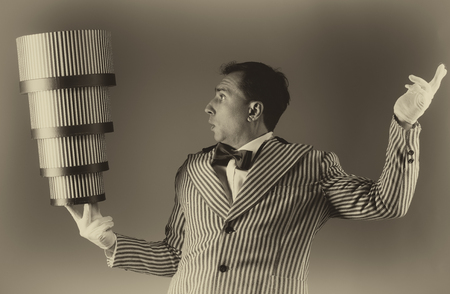 adroitness: Magician conjuring tricks with the stacked gift boxes. Pre-holiday shopping concept