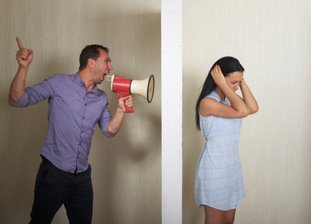 severance: Man shouts at woman through a megaphone, she covers her ears with the hands. Conflict concept