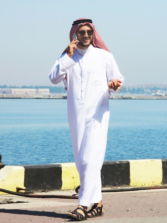 thobe: Arabian man talking on the cell phone in the port