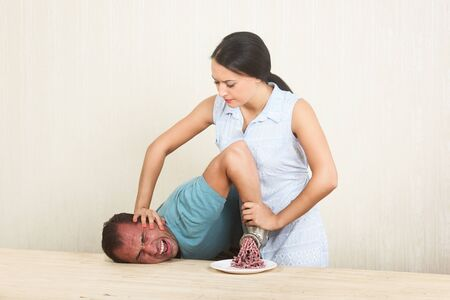 Woman chopping her boyfriends hand with a meat grinder