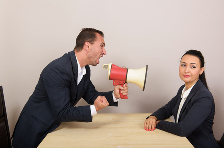 insist: Man shouts through a megaphone at the woman, but she ignores him