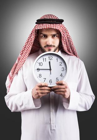thobe: Studio portrait of a serious Arabian man with the clock Stock Photo