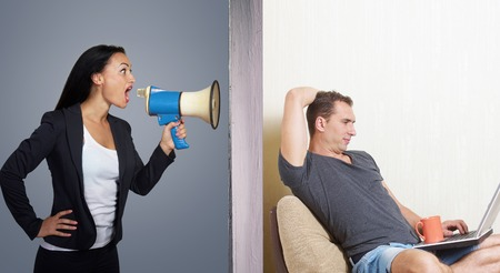 Man surfing the internet while angry woman calling him through a megaphone Stock Photo