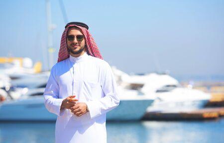 thobe: Arabian man looking at the yacht harbor