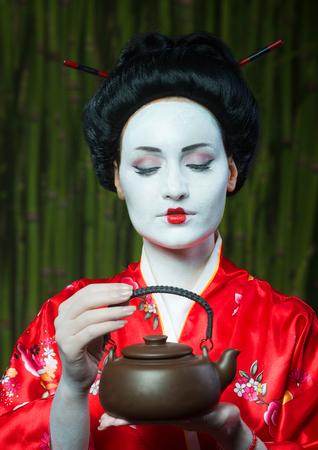 estereotipo: Mujer en maquillaje de geisha con tetera de arcilla Foto de archivo