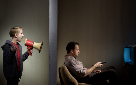 Man watching TV while his son calling him through a megaphone. Lack of fathers attention concept