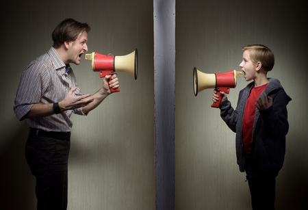 Tween son and his father yelling through the megaphones standing on either side of a wall Stock Photo