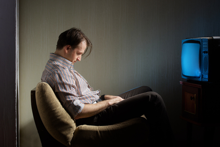 Man falling asleep in front of the TV Stock Photo