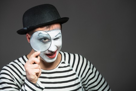 Male mime looking through the magnifying glass