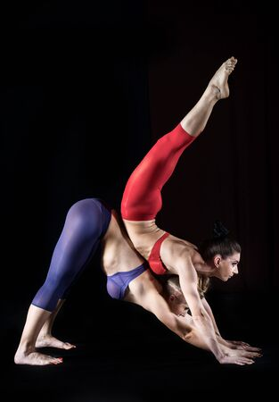 duo: Two women practicing gymnastic yoga, studio shot
