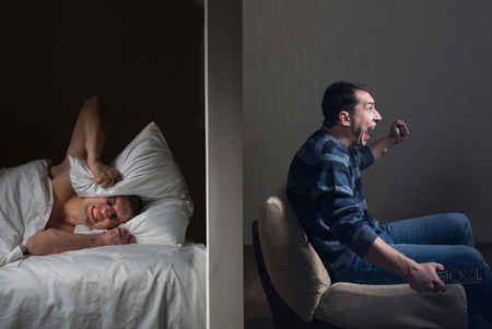 Man at night cant fall asleep because of the noisy neighbor