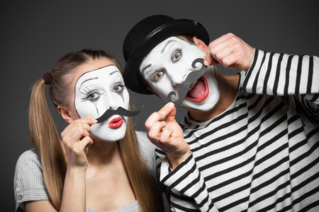 Couple of mimes with paper mustaches