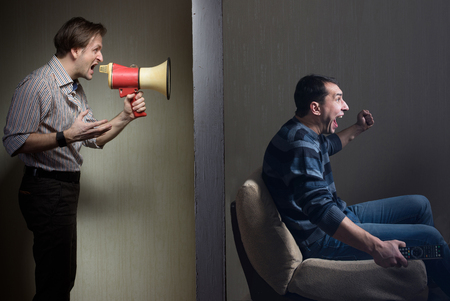 Man watching TV while angry man calling him through a megaphone