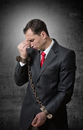 Shocked businessman with chained hands
