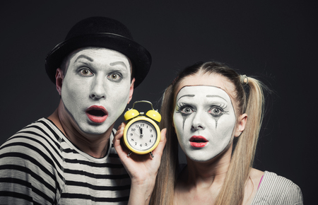 Funny couple of mimes with alarm clock looking at camera