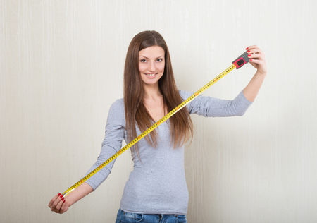 collapsible: Portrait of a smiling woman extending a tape measure out