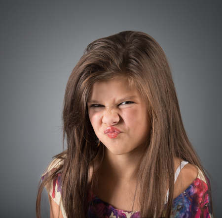 revulsion: Grimacing girl, studio shot, gray background Stock Photo