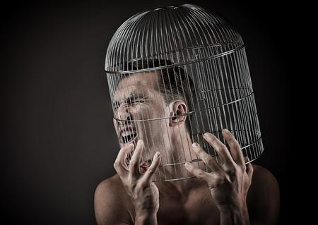 Man met het hoofd in een vogelkooi, concept Stockfoto