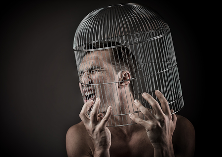 Man with the head inside a birdcage, concept Stock Photo