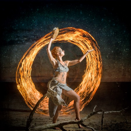 Portrait of a body painted girl dancing with the flame