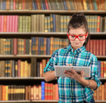 electronic book: Preteen girl looking at a Tablet PC screen, library background Stock Photo