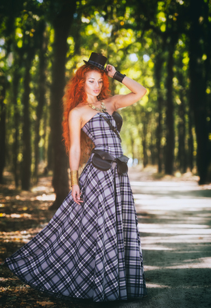 Portrait of a beautiful redheaded steampunk woman in the forest