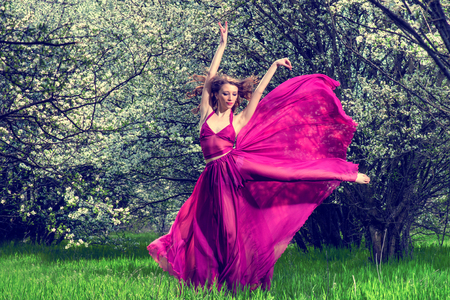 Romantic portrait of the woman in airy crimson dress dancing among the blossoming trees