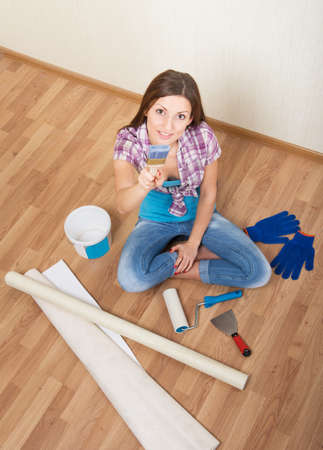 Woman sitting on the floor among the decorating tools