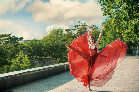 Romantic portrait of the woman in airy red dress dancing on the boulevard Stock Photo
