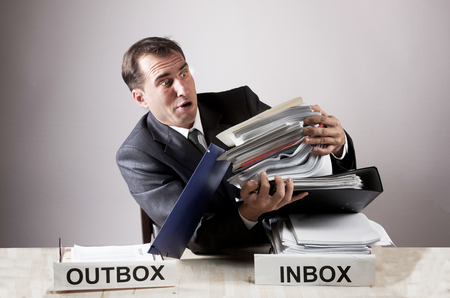 Stressed office worker with a paper stack Stock Photo