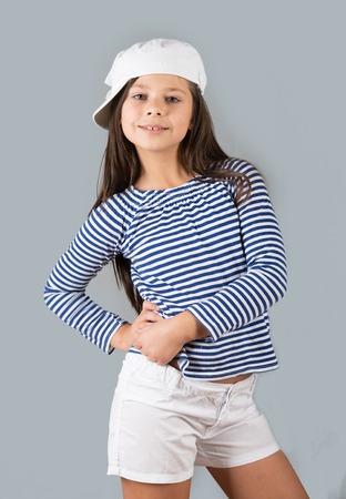 Portrait of a cheerful preteen girl, studio shot, gray background 版權商用圖片