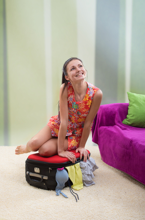overfilled: Girl trying to close her stuffed suitcase Stock Photo