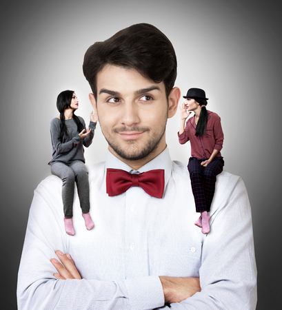 Portrait of a young man in a bow tie with two talking women sitting on his shoulders Stock Photo