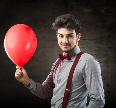 Smiling man with a red balloon Stock Photo