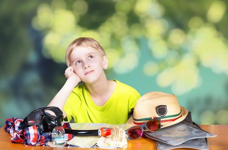snění: Chlapec sedí u stolu a sní o dovolené na pláži Reklamní fotografie