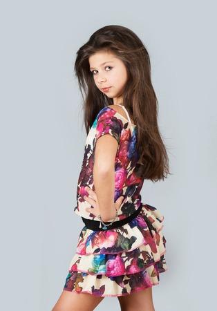 Fashionable preteen girl posing for photo, studio shot, gray background Stok Fotoğraf