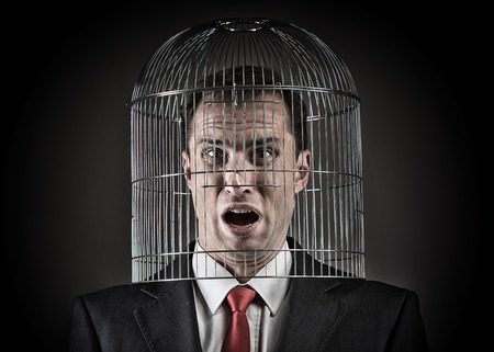 Office worker with the head inside a birdcage, concept Stock Photo