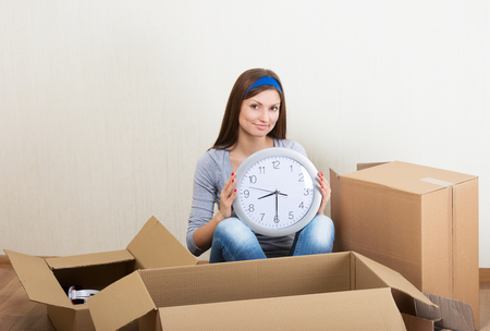 Smiling woman with the clock sitting on the floor among the moving boxes Stock Photo