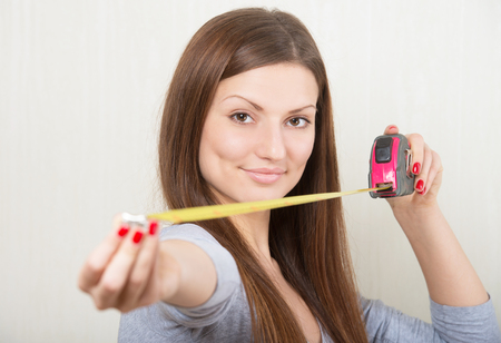Portrait of a smiling woman extending a tape measure out photo