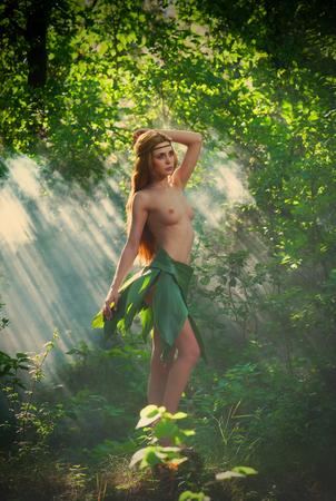 대나무 숲에서 춤추는 잎 치마를 입은 벌거 벗은 여자 님프 스톡 콘텐츠